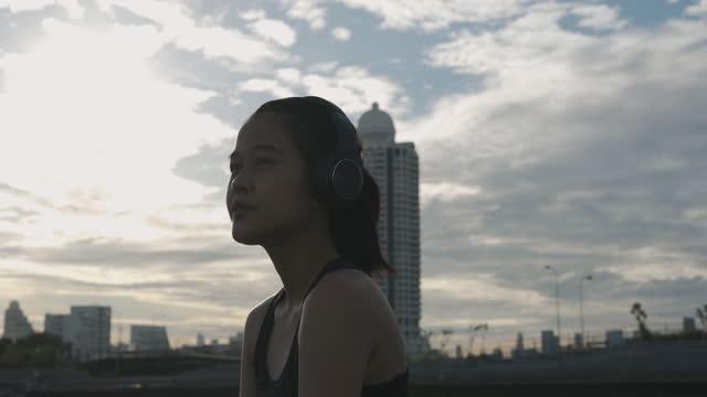 ヘッドフォンから音楽を聴くアジアのスポーツ女性 - 女子トラック競技点の映像素材/bロール