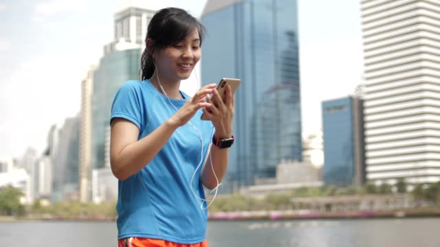 asian sport woman walking and using smart phone in city - athleticism stock videos & royalty-free footage