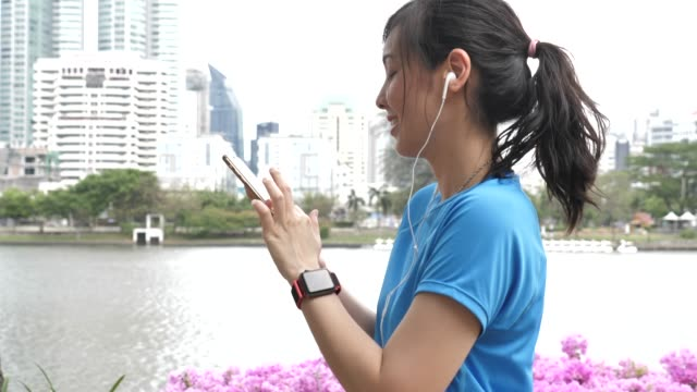 asian sport woman walking and using smart phone - fitness tracker stock videos and b-roll footage
