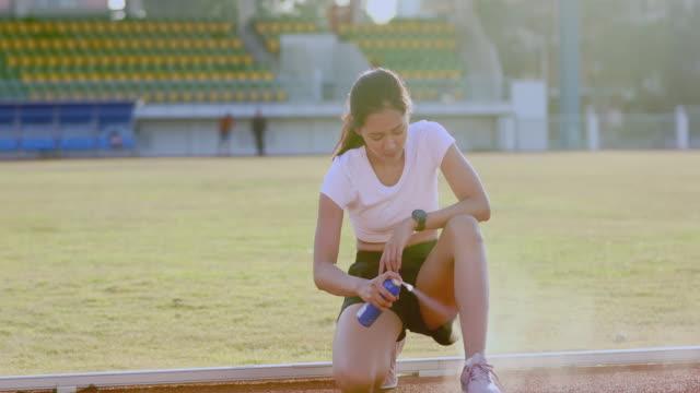 vídeos de stock e filmes b-roll de asian sports women using freezing spray for treating injured sportwomen's knee and leg after run - pulverizar