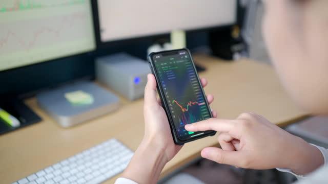 vídeos de stock, filmes e b-roll de investidores asiáticos vestindo um terno branco no quarto da casa veja gráficos de ações na tela do computador e tablet. - comercializar