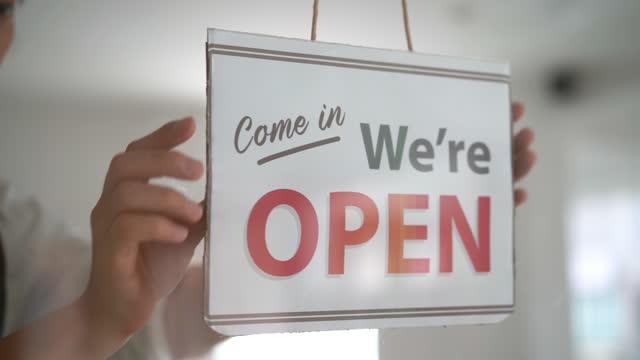 dipendente negozio asiatico mettendo in attività segno aperto sulla porta di vetro - insegna di negozio video stock e b–roll