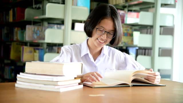 vídeos de stock, filmes e b-roll de livro de leitura rapariga estudante asiática na biblioteca pública - povo tailandês