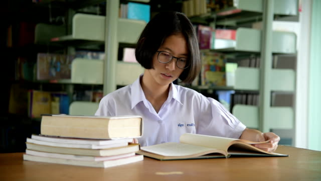 asian student girl reading book in public library - thai culture stock videos & royalty-free footage