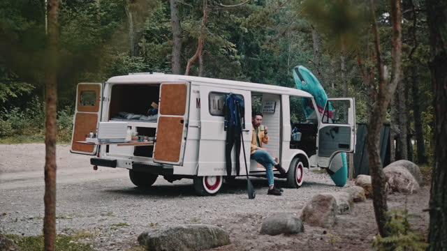 asian surfer drinks coffee in the morning during family road trip with mini van - camping stock videos & royalty-free footage