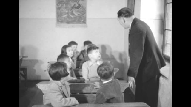 vídeos de stock, filmes e b-roll de asian teacher talking to young students / closer view children listening / ms boy children seated around him / cu teacher / quick shot large building... - documentário cinematográfico