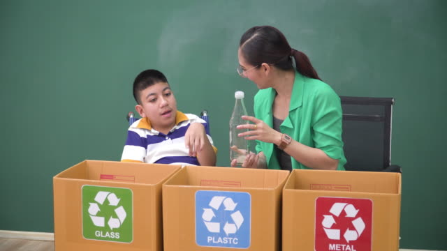 asian teacher teaching a disability boy student in a wheelchair to learn how to separate recycle waste, glass, metal, and plastic in the classroom. concept of child education about sustainability and boy power to social responsibility. - disability awareness stock videos & royalty-free footage