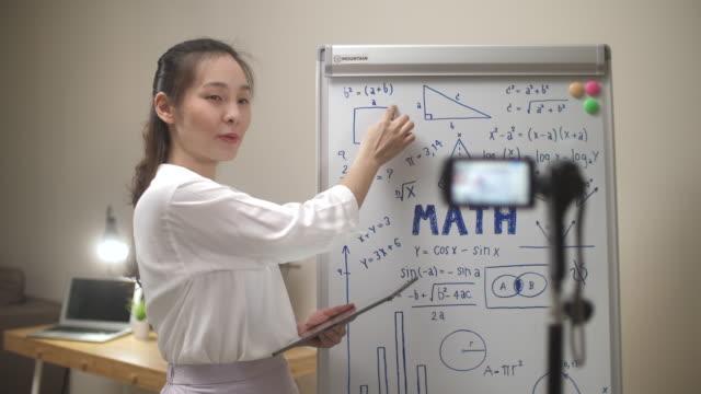 vídeos de stock e filmes b-roll de asian teacher woman online teaching with her camera at home - aula de formação