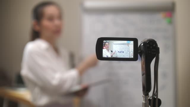 vídeos de stock e filmes b-roll de asian teacher woman online teaching with her camera at home - workshop