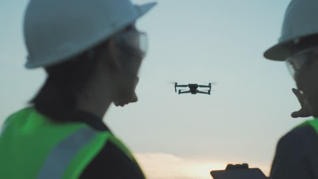 stockvideo's en b-roll-footage met aziatische teamingenieur operate vliegende drone boven olieraffinaderij fabriek. - hoofddeksel
