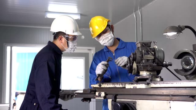 asian team maintenance wear with safety vest and yellow helmet  wearing face mask using machinery in manufacturing plant - trainee stock videos & royalty-free footage
