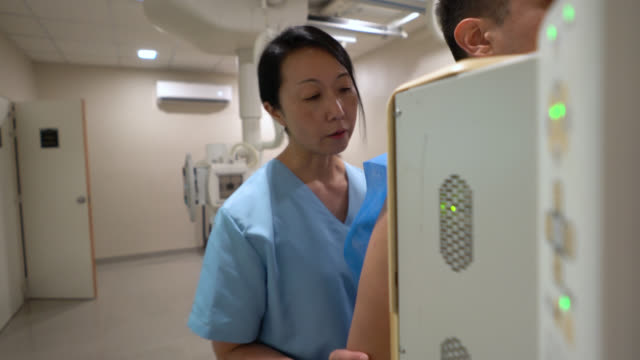 asian technician taking a chest xray to a male patient - chest torso stock videos & royalty-free footage
