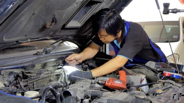 アジアの技術者がエンジンを修復しています。 - 作業場点の映像素材/bロール