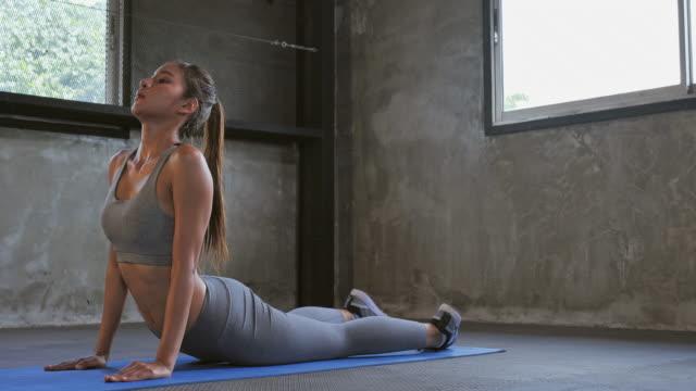 vídeos de stock, filmes e b-roll de músculos da parte traseira do executivo da menina adolescente asiática na ginástica, um exercício na ginástica. - tatame equipamento para exercícios