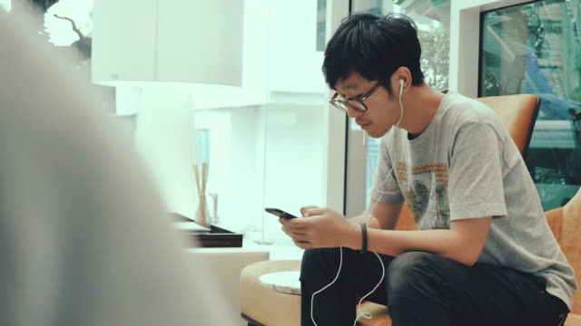 asian teenage boy listening to music with earphones on mobile phone. - 20 29 years stock videos & royalty-free footage