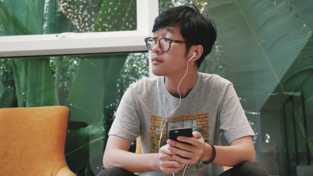 アジア 10 代の少年は、携帯電話にイヤホンで音楽を聴きます。