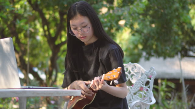 asian teenage girl e-learning ukulele in backyard - seat stock videos & royalty-free footage