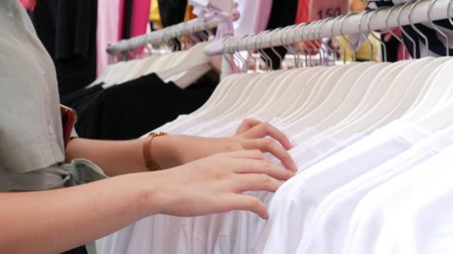 stockvideo's en b-roll-footage met aziatische tiener die kleding in kleinhandelswinkel winkelt - alleen één tienermeisje