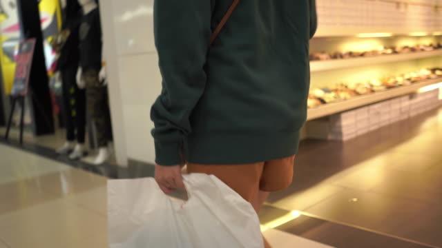 ショッピングモールで買い物袋を持って歩くアジアの十代の少女 - 買い物袋点の映像素材/bロール