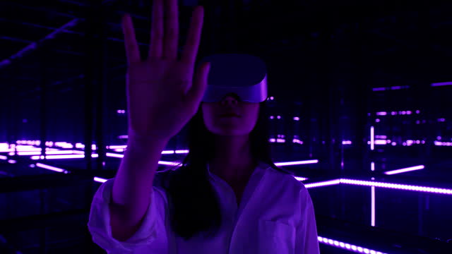 asian teenage girl wearing virtual reality headset and gesturing while touching air during the vr experience in colourful uv lighting at dark night.virtual reality concept. - interactivity stock videos & royalty-free footage