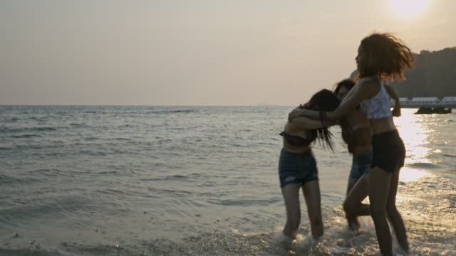 asian teenage girls dancing playfully tease each other on the beach with beautiful sea in thailand. - uv protection stock videos and b-roll footage