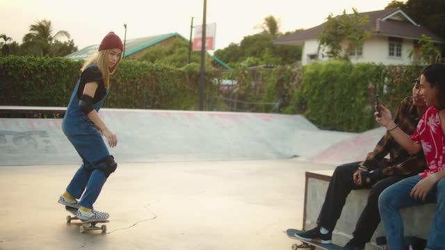 gruppo adolescente asiatico che cavalca skateboard nello skate park. - stunt video stock e b–roll
