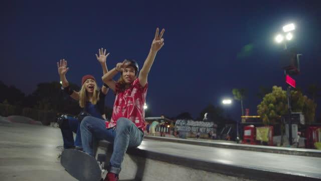 stockvideo's en b-roll-footage met aziatische tienergroep die skateboards op concrete vloer berijdt. - skateboardpark