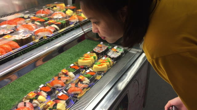 asian teenage woman shopping in supermarket - sushi video stock e b–roll