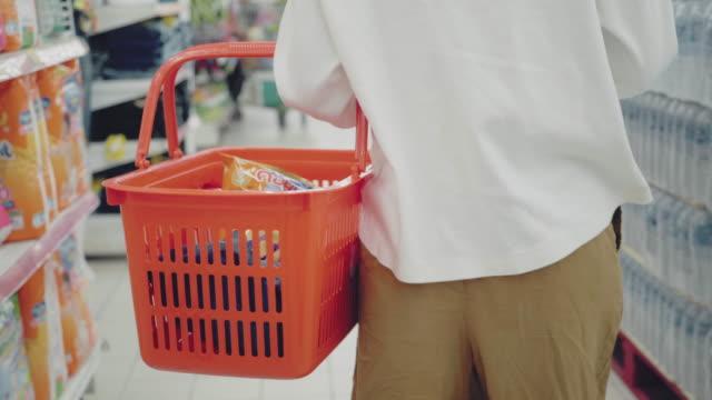 stockvideo's en b-roll-footage met aziatische tienerdie in supermarkt met gezichtsmaskerbescherming winkelt - vermijden
