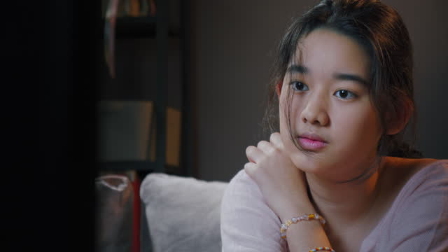 asiatische teenager mädchen fühlen sichweile beobachten film oder wechseln kanal, während fernsehen auf dem sofa zu hause - fade in video transition stock-videos und b-roll-filmmaterial