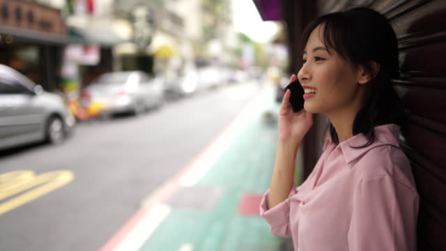 asian teenager girl making a phone call in city street - generation z stock videos & royalty-free footage