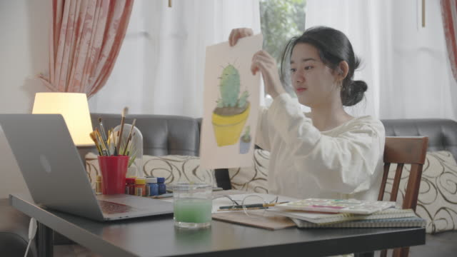 asian teenager girl using laptop computer having video call talking and smiling with her friends at home while painting watercolor. she using video conference chatting on vlog social media. technology and social teleconferencing concepts. - art stock videos & royalty-free footage