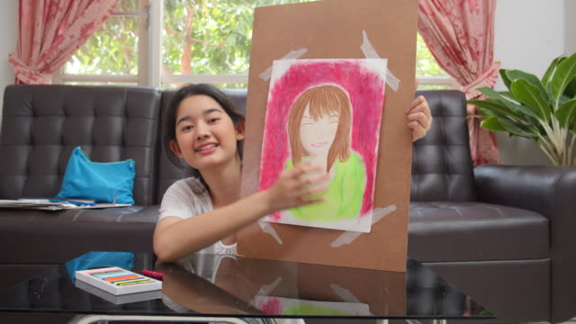 asian teenager kid girl showing her finished drawing and painting art and craft in the living room while staying at home. she using oil pastel or chalk color to create art project in to white paper form her imagination. art and crafts concepts. - chalk art equipment stock videos & royalty-free footage