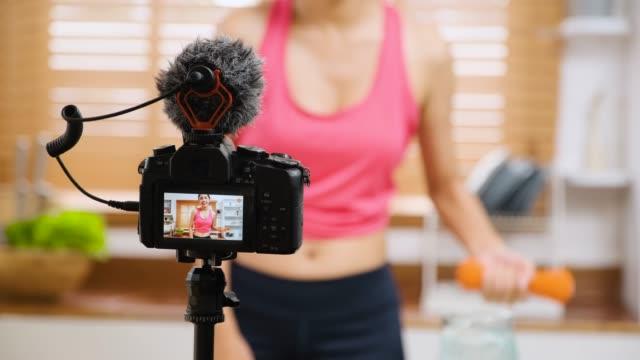 vidéos et rushes de asiatique thai sport femme vlogger haltère exercice à la caméra vidéo dans la cuisine tout enregistrer vlog sain. concept de style de vie influenceur. focus à la caméra - sans mise au point and équilibre