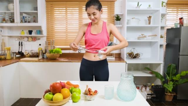 vidéos et rushes de asian thai sport femme vlogger sourire à la caméra vidéo dans la cuisine tout enregistrer vlog sain. concept de style de vie influenceur - blog vidéo