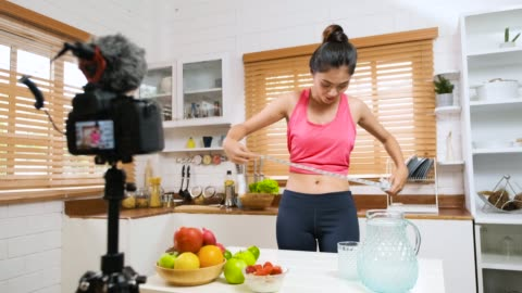 asian thai sport woman vlogger smile at video camera in kitchen while record healthy vlog. influencer lifestyle concept - tape measure stock videos & royalty-free footage