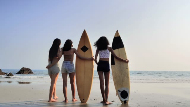 asian three beautiful young women surfer girls in bikinis with white surfboards at a beach.sports cinemagraphs - surfboard stock videos & royalty-free footage