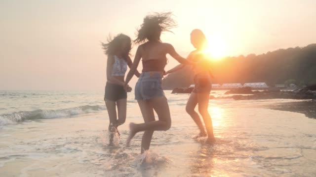 asian three young female friends having fun at sunset beach.beach holidays travel concept.travel cinemagraphs - beach holiday stock videos & royalty-free footage