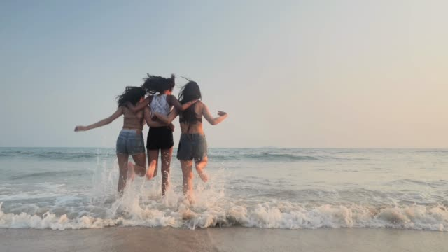 asian three young female friends having fun at sunset beach.beach holidays travel concept.travel cinemagraphs - back lit woman stock videos & royalty-free footage