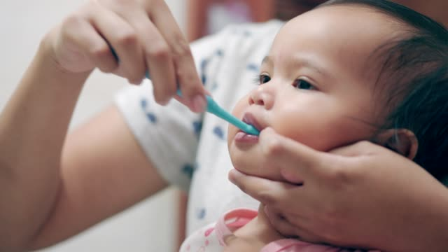 asian toddler being brushed teeth by her mother in the bathroom - toothbrush stock videos & royalty-free footage