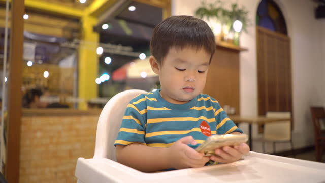asian toddler using a smartphone on a high chair at the restaurant - interactivity stock videos & royalty-free footage