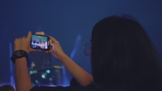 vidéos et rushes de touriste asiatique capturant la vie de ville la nuit dans la ville de bangkok. - photo messaging