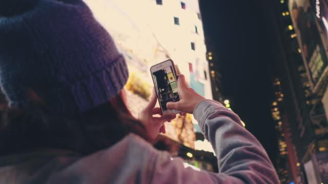 asiatische touristen erfassung stadtleben in der nacht im time square. - kreativer beruf stock-videos und b-roll-filmmaterial