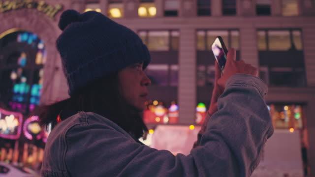 asiatiska turister fånga stadslivet på natten i time square. - back lit bildbanksvideor och videomaterial från bakom kulisserna