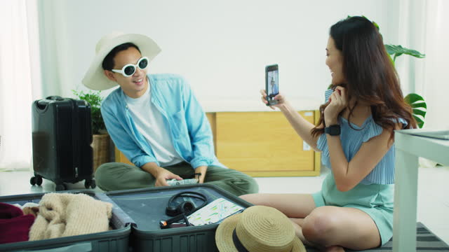 vídeos de stock e filmes b-roll de asian tourist couple planning travel selfie photo and packing suitcases for travel before travel date at home background.concept of safe tourism after the covid 19 outbreak.4k uhd. - temas fotográficos