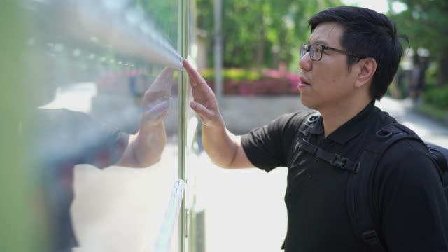vídeos y material grabado en eventos de stock de hombre turista asiático comprando bebidas enlatadas de vending machine - carbonatada