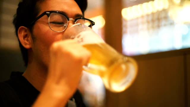 asian tourist man drinking japanese beer in restaurant - beer glass stock videos & royalty-free footage