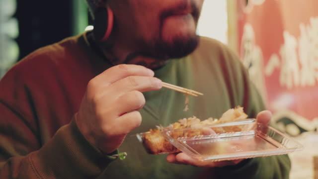 夜に東京の路上で食べるアジアのツーリストマン。 - ダンプリング点の映像素材/bロール