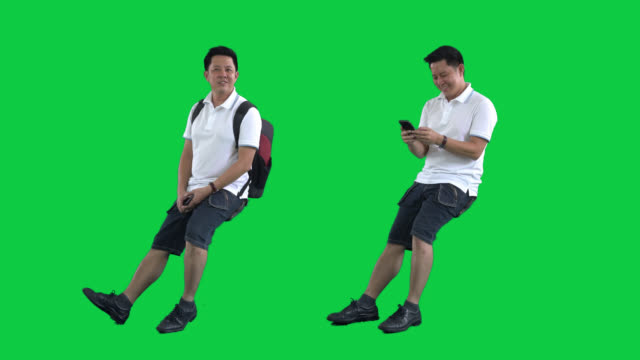 asian tourist man on green screen ,4k footage with alpha chanel.codeck-png+alpha. - sitting video stock e b–roll