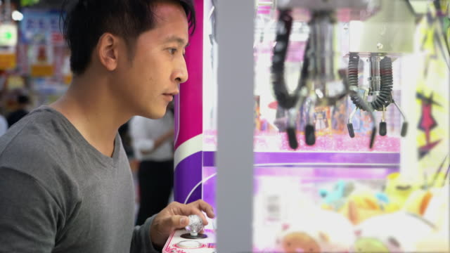 Asian tourist man using Japanese arcades to play crane game claw machines
